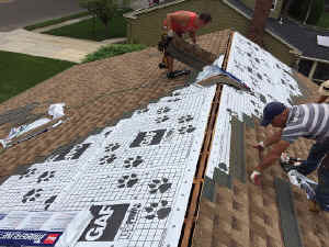 employees installing new shingles on a roof